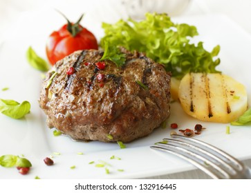 Delicious grilled beef meatball served on a white plate with tomato and lettuce with a fork in the foreground