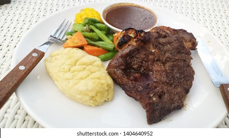 delicious grilled beef striploin steak with black pepper sauce and various vegetable on the white plate