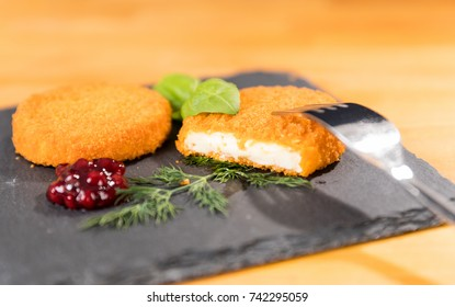 Delicious grilled Camembert cheese with cranberry sauce, decorated with basil leaves and dill, on a slate plate. Shallow depth of field.
