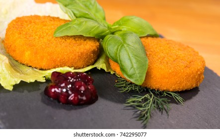 Delicious grilled Camembert cheese with cranberry sauce, decorated with salad, basil leaves and dill, on a slate plate.
