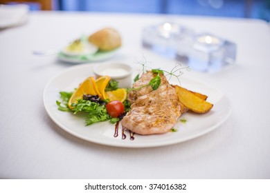 Delicious grilled chicken breasts with potatoes and colorful garnish