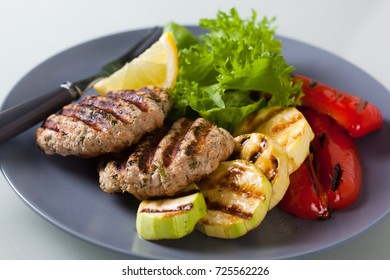 Delicious grilled chicken burgers served with fresh salad and grilled vegetables