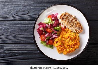 Delicious grilled chicken with garnish of sweet potato and fresh salad close-up on a plate on the table. horizontal top view from above