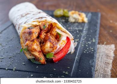 Kebab-Verpackung mit Zwiebeltomate und Petersilie auf schwarzem Steinplatte.