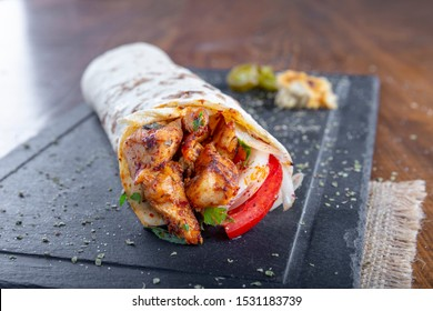 Delicious grilled chicken kebab wrap with onion tomato and parsley on black stone plate.