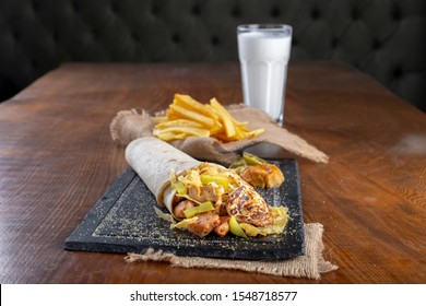 Delicious grilled chicken kebab wrap roll with melting cheese, sliced pickles, grated potato chips, aubergine salad on top , french fries and Turkish yogurt drink Ayran at black stone plate.