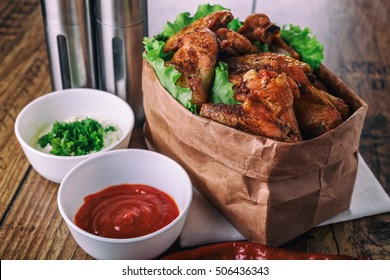 delicious grilled chicken wings with garlic and tomato sauce with lettuce in food paper bag on wooden rustic background top view, witi copyspace