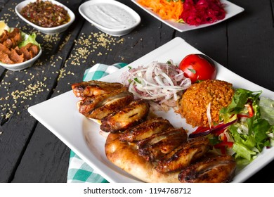 Delicious Grilled Chicken Wings Kebab with bulgur pilaf, onion and salad on rustic black wooden table background. Dark photography concept.