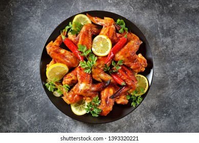 Delicious grilled chicken wings with lemon juice and chili pepper on gray concrete background. Top view.