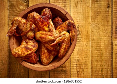 Delicious grilled chicken wings in a wooden bowl on old wooden table.