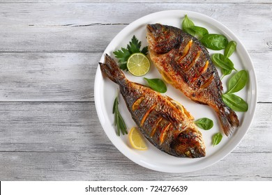 delicious grilled dorado or sea bream fish with lemon and orange slices, spices, fresh parsley and spinach on white platter on old wooden table, horizontal view from above
