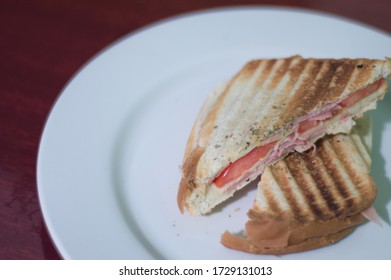 delicious Grilled ham and cheese, with tomatoes on a white plate, toast, practical and fast food for hunger