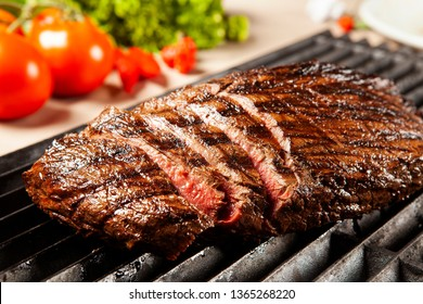 Delicious grilled meat over the grill on a barbecue