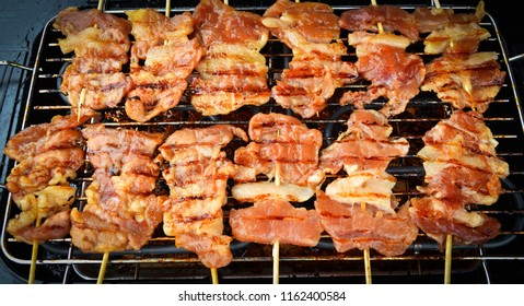 Delicious Grilled pork bamboo sticks on grille /Thai street food.