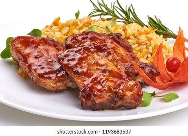 Delicious grilled pork ribs in BBQ sauce with pilaf, isolated on white background. Close-up.