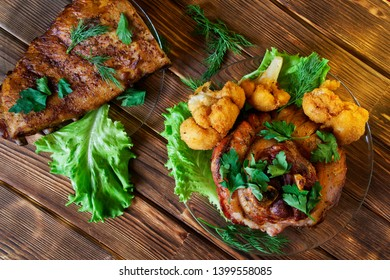 Delicious grilled pork ribs and knuckles, seasoned with parsley, lettuce, cauliflower and dill. Baked meat lies on a wooden rustic table made of natural pine boards. Daylight.