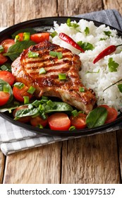 Delicious grilled pork steak with rice and fresh vegetable salad close-up on a plate on the table. vertical