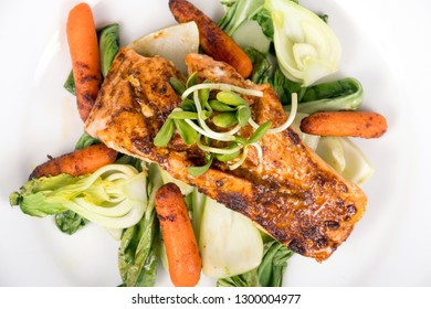 Delicious grilled salmon dish over bokchoy cabbage and roasted baby carrots plate