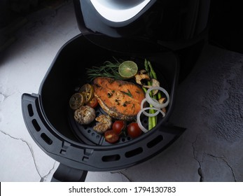 Delicious Grilled Salmon fillet with thyme, garlic and lemon slices,shiitake mushroom  tomatoes in air fryer. clean and healthy food in dark tone.