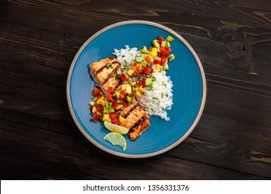 Delicious grilled salmon steak on a blue plate with jasmine rice and sauce made of mango, bell pepper, onion and avocado. Top notch food. Top view shot above.