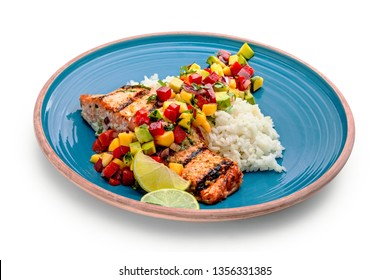 Delicious grilled salmon steak on a blue plate with jasmine rice and sauce made of mango, bell pepper, onion and avocado. Top notch food, isolated on white.