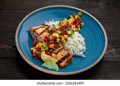 Delicious grilled salmon steak on a blue plate with jasmine rice and sauce made of mango, bell pepper, onion and avocado. Top notch food on a wooden table.