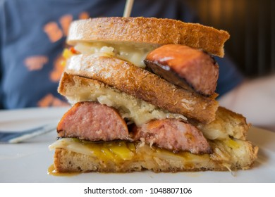 Delicious grilled sandwich with sausage, cheese and sauerkraut