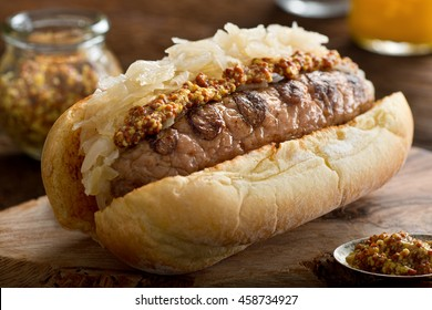 A delicious grilled sausage with sauerkraut and coarse mustard on a toasted hot dog bun.
