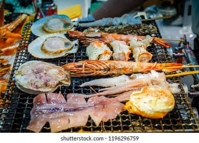 Delicious grilled squid street food at Kuromon Ichiba Market, Osaka. Delicious grilled scallop at a food stall in Osaka. Various Japanese grilled for sale at Kuromon ichiba market