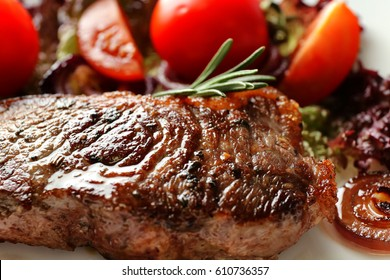 Delicious grilled steak with aromatic rosemary, tomatoes and onion, closeup