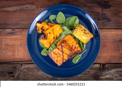 delicious grilled tofu slices with corn and yellow bell pepper dish over a pinach bed