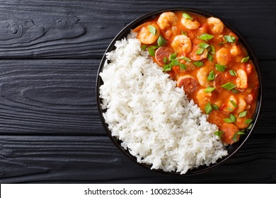 Delicious gumbo with prawns, sausage and rice on a plate on the table. horizontal top view from above