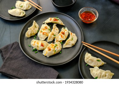 Delicious gyoza dumplings  on black plates  with soy sauce and chili oil. selective focus