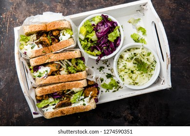 delicious gyros sandwich in paper bag with salad and tzatziki, top view,