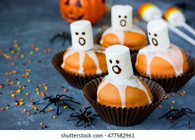 Delicious Halloween treat for dessert, pumpkin chocolate muffins with sweet white marshmallow ghosts selective focus
