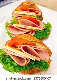 Delicious ham and cheese croissants in a white plate with green lettuce red tomato slices colorful beautifully decoration healthy breakfast home baked pastry croissant sandwich