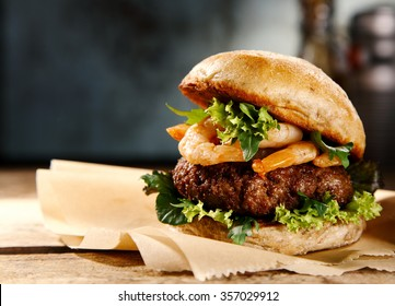 Delicious hamburger with beef and grilled fresh shrimp garnished with lettuce served on pieces of brown paper on a rustic wooden counter, close up side view with copyspace