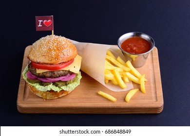Delicious hamburger with beef, onion, lettuce, tomato served with potato fries and ketchup on wooden board. Burger menu on a black background with a copy space.