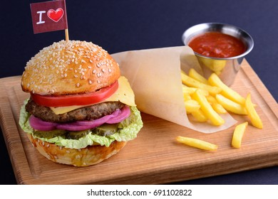 Delicious hamburger with beef, onion, lettuce, tomato served with potato fries and ketchup on wooden board. Burger menu on a black background with a copy space. Close up.