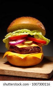 Delicious hamburger with cheese, pickles, tomato, onions and lettuce on wooden cutting board on dark table