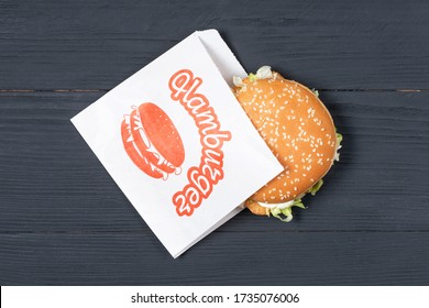 Delicious hamburger in classic paper bag on wooden background. concept of eco packages of recyclables. still life