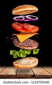 Delicious hamburger with flying ingredients on black background Flying burger ingredients