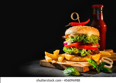 Delicious hamburger with french fries and ketchup on dark background