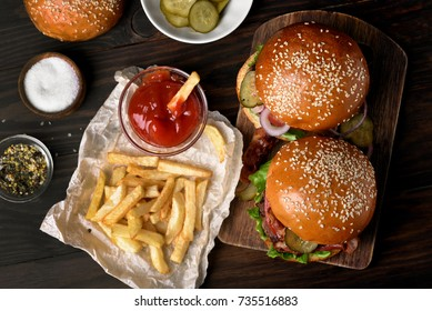 Delicious hamburger and french fries on wooden background. Top view, flat lay