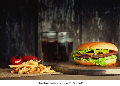 Delicious hamburger with french fries, tomatoes and cold drink
