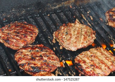 Delicious hamburger patties on a metal grill with fire under