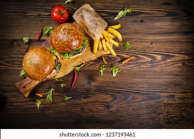 Delicious hamburgers with fries, served on wood. Top view. Free space for text