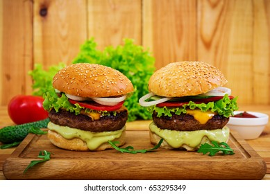 Delicious hand made burger on wooden background. Close view