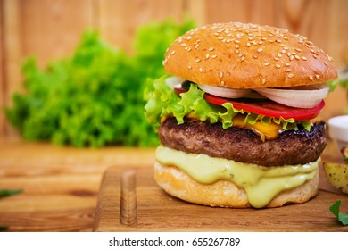 Delicious handmade burger on wooden background. Close view