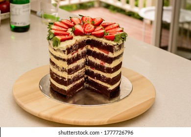 Delicious handmade double barrel tall layered cake decorated with strawberries on a cake stand
